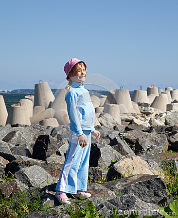Little girl in tracksuit stand on rocks