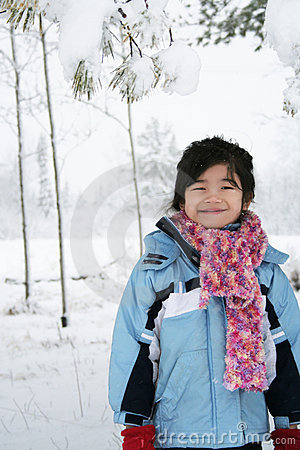 Little girl under snow covered trees