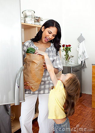 Little girl unpacking grocery bag with her mother