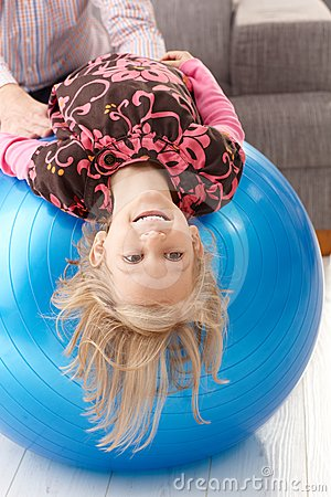Little girl upside down on fit ball laughing