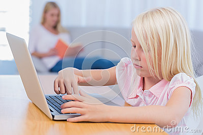 Little girl using laptop while her mother is reading on the couc