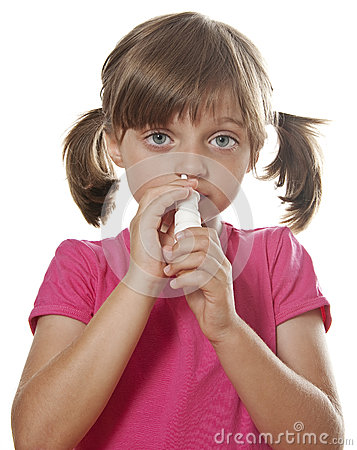 Little girl using nasal spray