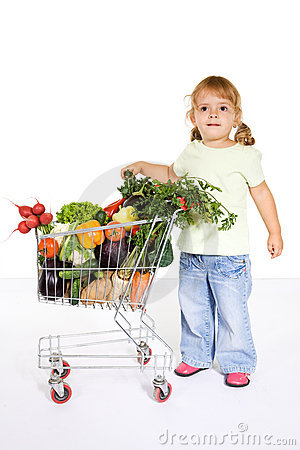 Little girl with vegetables in a shopping cart