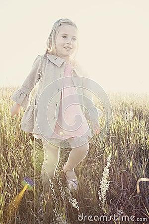 Little girl walking through field