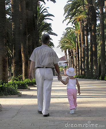 Little girl walking in a park with her grandfather
