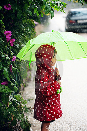 Little girl walking in the rain
