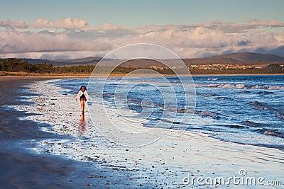 Little girl walking on shore at sunset