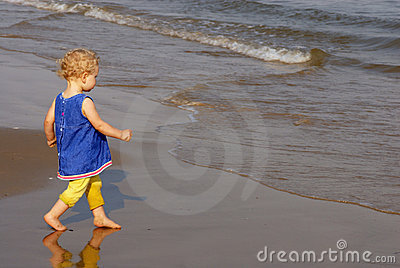 Little girl walking towards the seashore
