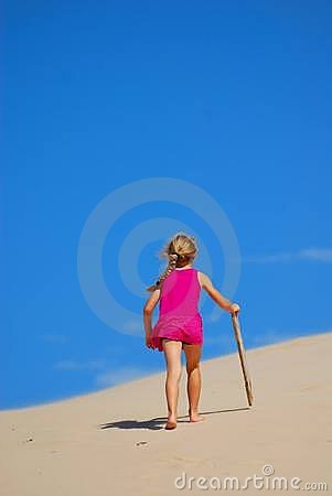 Little girl walking up sand dune