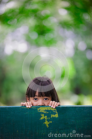 Little girl was hiding behind a chair in the park