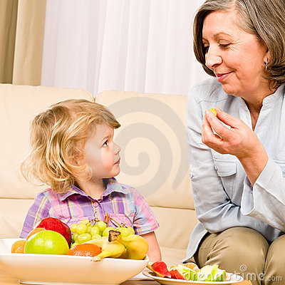Little girl watch grandmother eat fruit