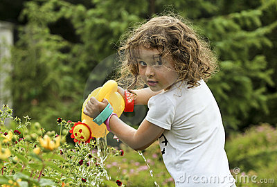 Little girl is watering the flowers in the garden