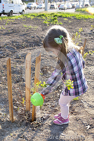 Free Little Girl Watering Newly Planted Tree Stock Photo - 93347970