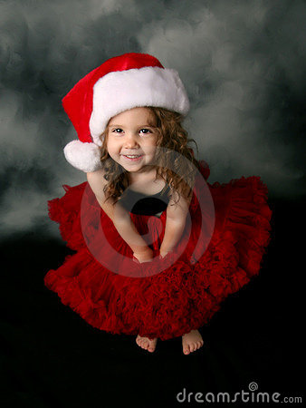 Little girl wearing Christmas santa hat and skirt