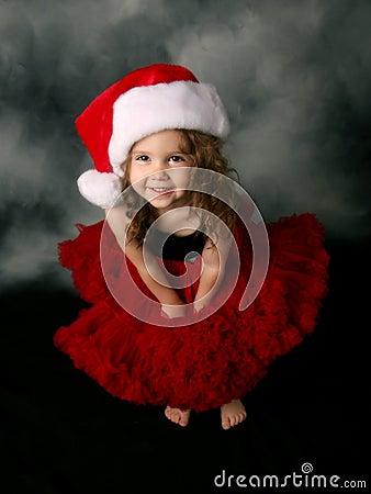 Little girl wearing Christmas santa hat and skirt