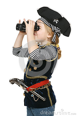 Little girl wearing costume of pirate looking away through the binoculars