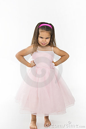 Little girl wearing pink dress pouting.