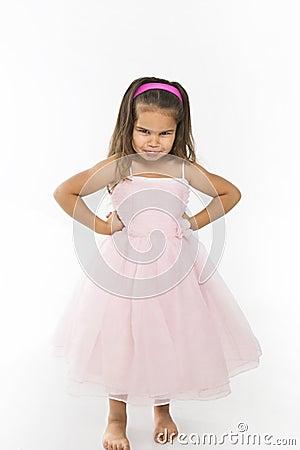 Little girl wearing pink dress pouting.