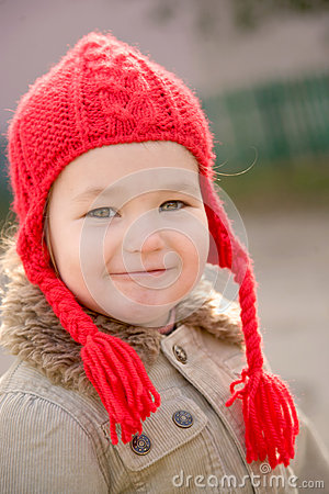 little girl wearing a red hand knitted hat