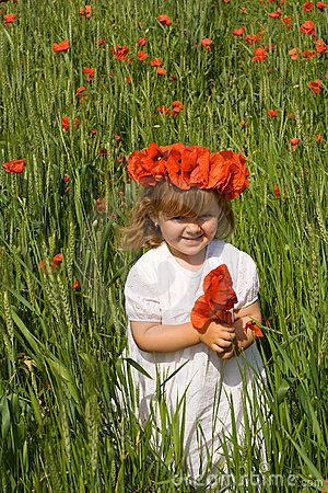 Little girl on wheat field with poppies