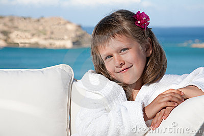 Little girl in white bathrobe relaxing on terrace