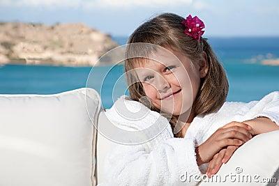 Little girl in white bathrobe relaxing on terrace