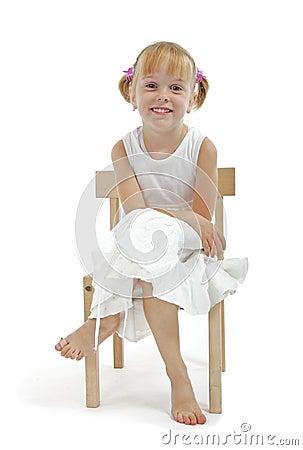Little Girl In White Dress Sitting On Wooden Chair Stock
