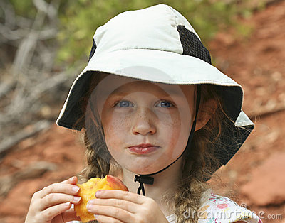 Girl In A White Hat Eating A Peach Stock Photos - Image: 20767763