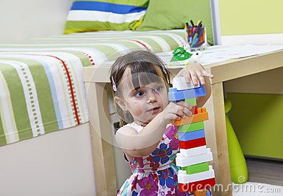 Little girl who builds castles with plastic cubes