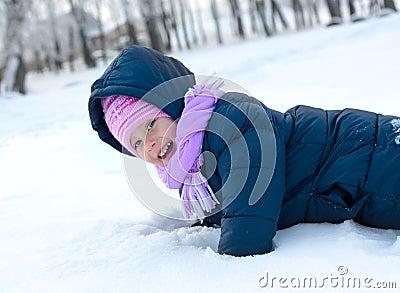 Little girl in winter pink hat in snow park