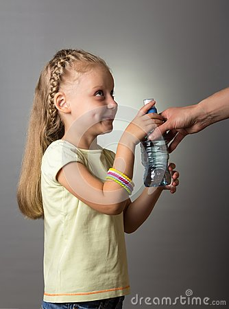 Free Little Girl With Beautiful Hair Takes From An Adult A Bottle Of Water Stock Photos - 103338743