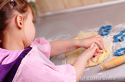 Little girl works with the dough in the kitchen