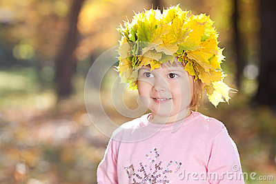 Little girl in a wreath of maple leaves