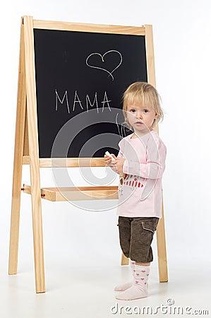 Little girl writing on a blackboard