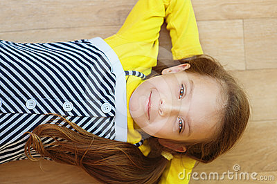 Little girl in yellow dress lying