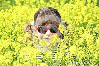 Little girl in yellow flowers field
