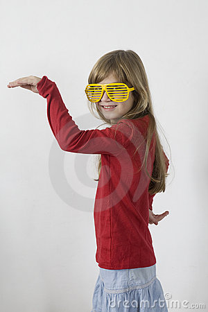 Little girl in yellow sunglasses dancing
