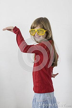 Little girl in yellow sunglasses dancing