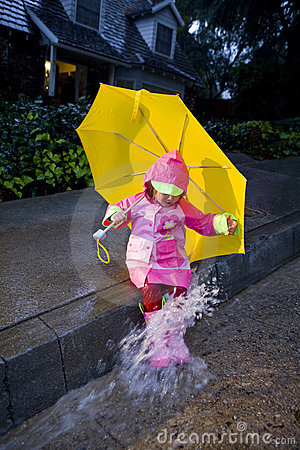Little girl with yellow umbrella playing in rain 4