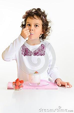 Little girl, yoghurt and strawberry