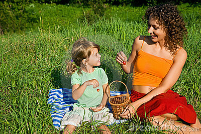 Little Girl and Young Women in hand sweet cherries