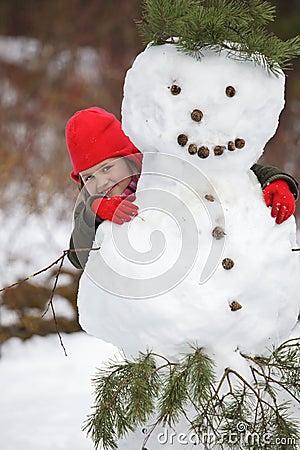 Little girlposing with snowman