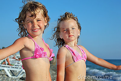 Little girls on beach, placed hands in sides