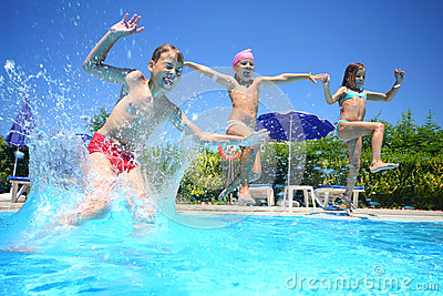Little girls and boy fun jumping into the swimming pool