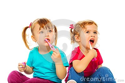 Little girls brush their teeth