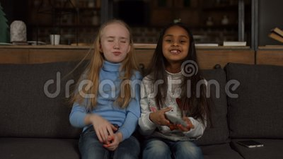 Little girls on the couch switch TV channels stock footage