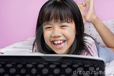 Little girls laughing while watching laptop
