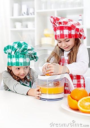 Little girls making fresh orange juice