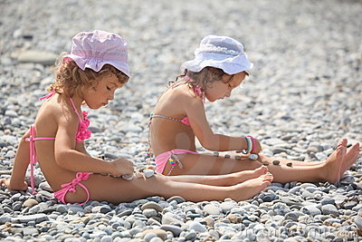 little girls is playing with pebble stones.