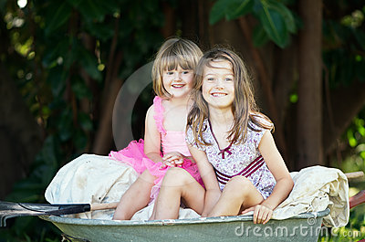 Little girls in wheelbarrow